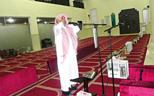 صورة لأحد المسلمين يؤذن للصلاة من داخل المسجد.