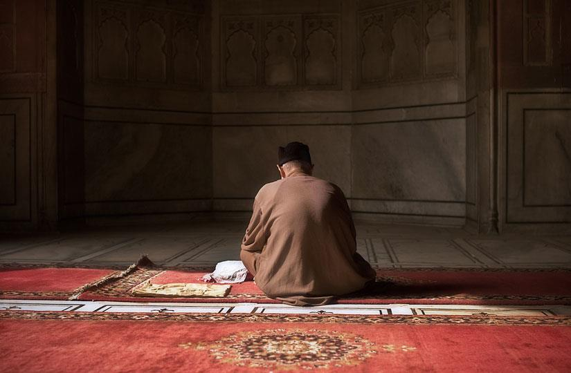 رجل جالس في مصلى في اتجاه القبلة.