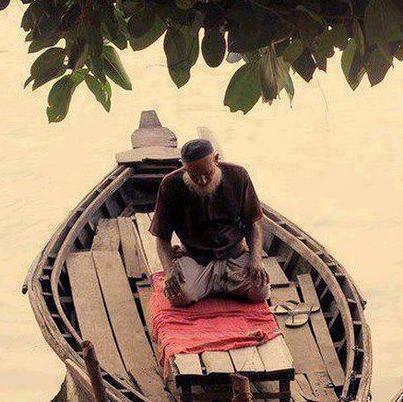 رجل يؤدي الصلاة على قارب.